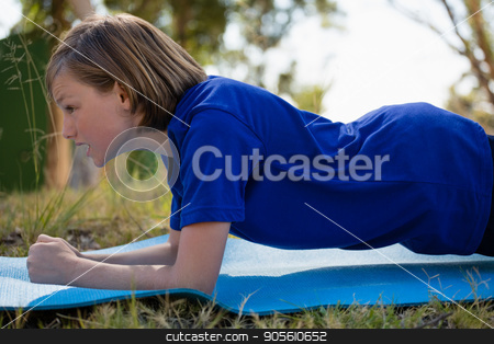 Girl exercising on exercise mat during obstacle course training stock photo, Girl exercising on exercise mat during obstacle course training in the boot camp by Wavebreak Media