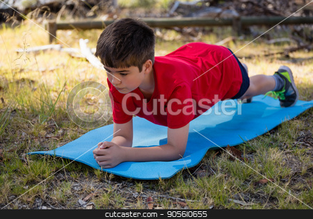 Boy exercising on exercise mat during obstacle course training stock photo, Boy exercising on exercise mat during obstacle course training in the boot camp by Wavebreak Media
