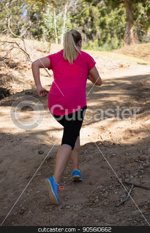 Woman jogging in the boot camp on a sunny day stock photo, Rear view of woman jogging in the boot camp on a sunny day by Wavebreak Media