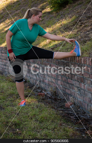 Woman performing stretching exercise during obstacle course training stock photo, Woman performing stretching exercise during obstacle course training in the boot camp by Wavebreak Media