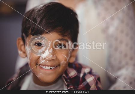 Portrait of smiling boy with flour on face stock photo, Portrait of smiling boy with flour on face at home by Wavebreak Media