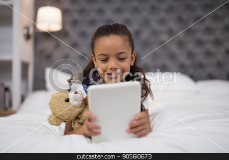 Little girl using digital tablet while lying on bed at home stock photo, Close up of little girl using digital tablet while lying on bed at home by Wavebreak Media