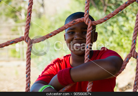 Portrait of happy boy leaning on net during obstacle course stock photo, Portrait of happy boy leaning on net during obstacle course in the boot camp by Wavebreak Media