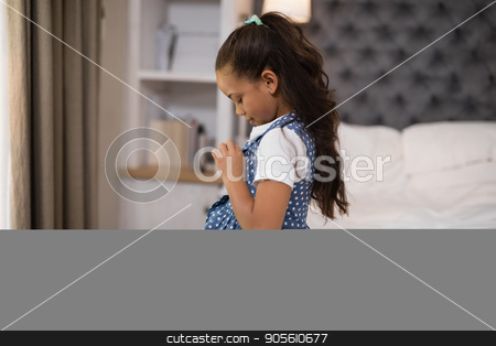 Girl dressing up while sitting on bed at home stock photo, Side view of girl dressing up while sitting on bed at home by Wavebreak Media