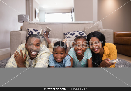 Smiling family watching television while lying on rug at home stock photo, Portrait of smiling family watching television while lying on rug at home by Wavebreak Media
