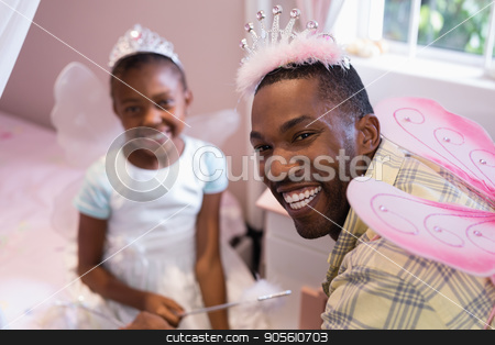 Cheerful father and daughter wearing costume wings at home stock photo, Portrait of cheerful father and daughter wearing costume wings at home by Wavebreak Media