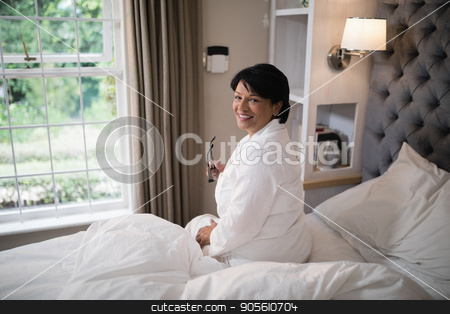 Smiling mature woman sitting in illuminated bedroom at home stock photo, Portrait of smiling mature woman sitting in illuminated bedroom at home by Wavebreak Media