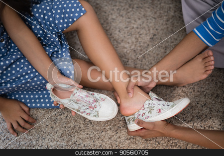 Cropped image of mother helping daughter to wear shoe stock photo, Cropped image of mother helping daughter to wear shoe at home by Wavebreak Media
