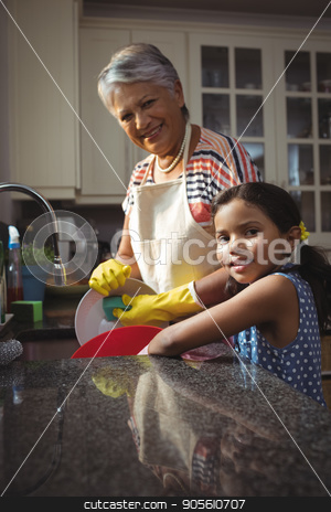 Grandmother and granddaughter washing utensil in kitchen sink stock photo, Portrait of grandmother and granddaughter washing utensil in kitchen sink at home by Wavebreak Media