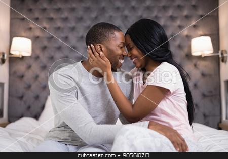 Happy young couple embracing in bedroom stock photo, Happy young couple embracing in bedroom at home by Wavebreak Media