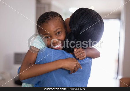 Happy girl embracing mother in living room at home stock photo, Portrait of happy girl embracing mother in living room at home by Wavebreak Media