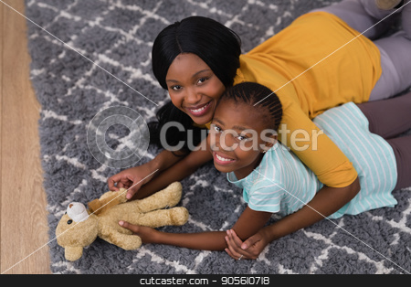 Mother and daughter with teddy bear while lying on rug at home stock photo, High angle view of mother and daughter with teddy bear while lying on rug at home by Wavebreak Media