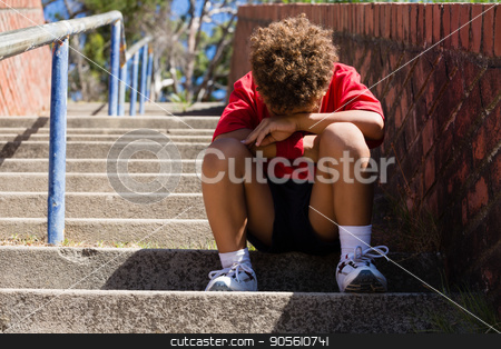 Upset boy sitting on staircase in the boot camp stock photo, Upset boy sitting on staircase in the boot camp on a sunny day by Wavebreak Media