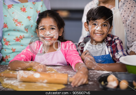 Portrait of smiling siblings with flour on face at home stock photo, Portrait of smiling siblings with flour on face standing in kitchen at home by Wavebreak Media