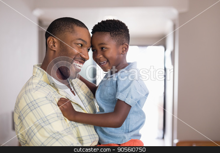 Father and son looking at each other in living room stock photo, Happy father and son looking at each other in living room by Wavebreak Media