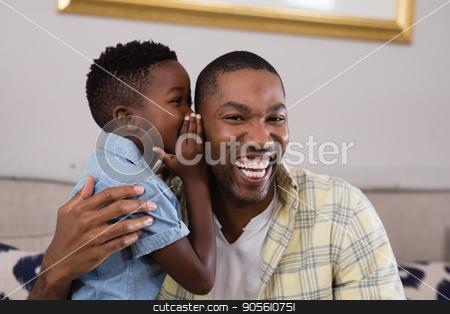 Boy whispering father on sofa at home stock photo, Little boy whispering father on sofa at home by Wavebreak Media