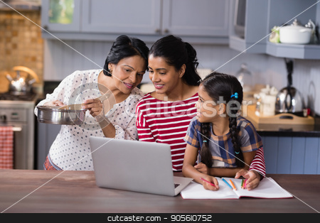 Multi-generation family using laptop in kitchen stock photo, Multi-generation family using laptop in kitchen at home by Wavebreak Media