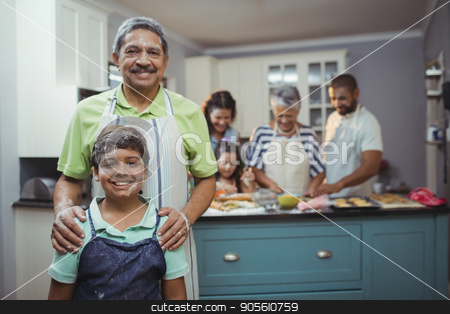 Grandfather and grandson smiling at camera while family members preparing dessert in background stock photo, Grandfather and grandson smiling at camera while family members preparing dessert in background at home by Wavebreak Media