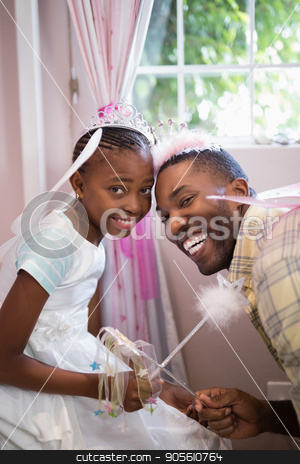 Cheerful father and daughter holding wands while wearing costumes stock photo, Portrait of cheerful father and daughter holding wands while wearing costumes by Wavebreak Media