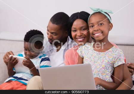 Happy family with laptop and digital tablet sitting on sofa stock photo, Happy family with laptop and digital tablet sitting on sofa at home by Wavebreak Media