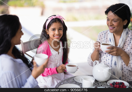 Portrait of smiling girl having breakfast with mother and grandmother stock photo, Portrait of smiling girl having breakfast with mother and grandmother at home by Wavebreak Media