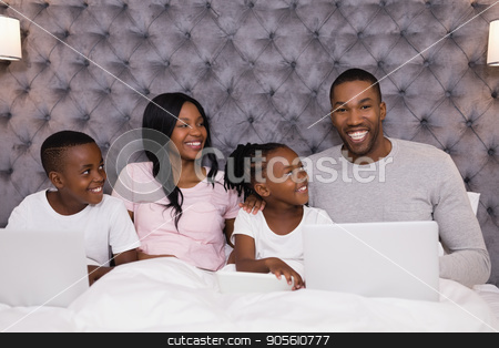 Portrait of smiling man using laptop while sitting with family on bed stock photo, Portrait of smiling man using laptop while sitting with family on bed in bedroom at home by Wavebreak Media
