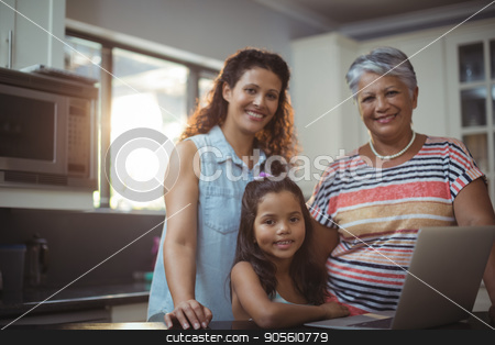 Happy family using laptop in kitchen stock photo, Portrait of happy family using laptop in kitchen at home by Wavebreak Media
