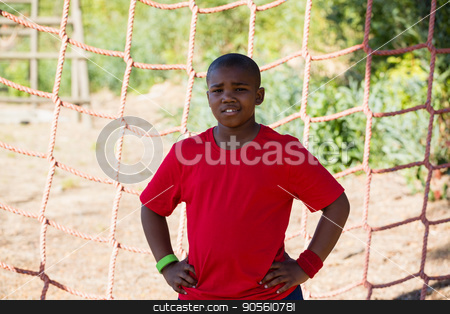 Boy standing with hands on hip during obstacle course training stock photo, Boy standing with hands on hip during obstacle course training in the boot camp by Wavebreak Media