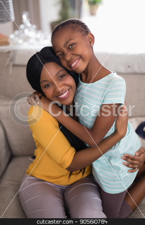 Smiling mother and daughter embracing on sofa at home stock photo, Portrait of smiling mother and daughter embracing on sofa at home by Wavebreak Media