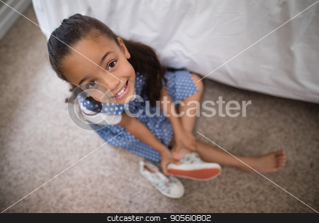Smiling girl wearing shoe at home stock photo, High angle view of smiling girl wearing shoe at home by Wavebreak Media