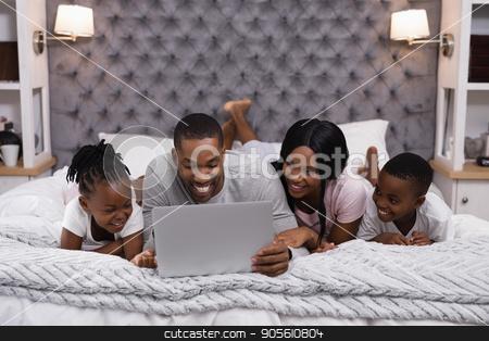 Smiling family using laptop while lying together on bed stock photo, Smiling family using laptop while lying together on bed at home by Wavebreak Media