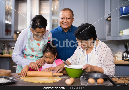 Portrait of smiling man with family preparing food in kitchen stock photo, Portrait of smiling mature man standing with family preparing food in kitchen at home by Wavebreak Media