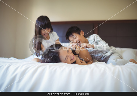 Happy family having fun on bed in the bed room stock photo, Happy family relaxing on bed in the bed room at home by Wavebreak Media
