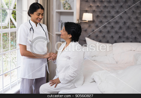 Smiling nurse comforting female patient on bed stock photo, Smiling nurse comforting female patient on bed at home by Wavebreak Media