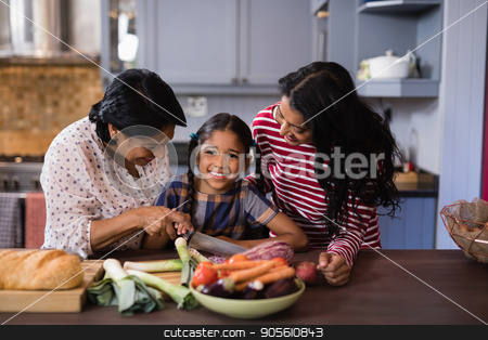 Portrait of girl preparing food with mother and grandmother in kitchen stock photo, Portrait of girl preparing food with mother and grandmother in kitchen at home by Wavebreak Media