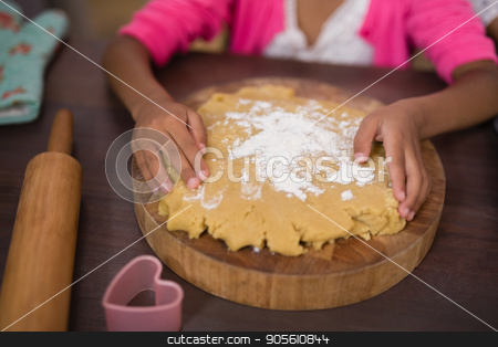 Mid section of girl touching dough in kitchen stock photo, Mid section of girl touching dough in kitchen at home by Wavebreak Media