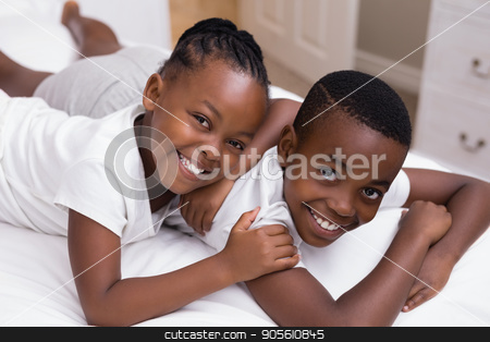 Portrait of smiling siblings lying on bed stock photo, High angle portrait of smiling siblings lying on bed at home by Wavebreak Media