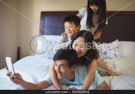 Happy family taking a selfie on mobile phone in the bed room stock photo, Happy family taking a selfie on mobile phone in the bed room at home by Wavebreak Media