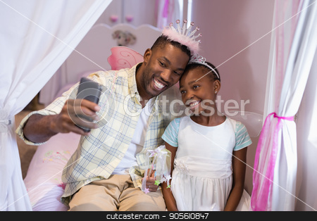 Father and daughter taking selfie while sitting on bed at home stock photo, Happy father and daughter taking selfie while sitting on bed at home by Wavebreak Media