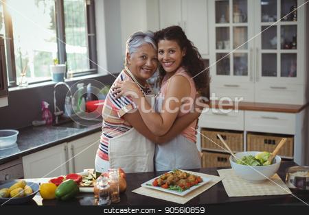 Mother hugging daughter in kitchen stock photo, Portrait of mother hugging daughter in kitchen at home by Wavebreak Media