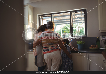 Little girl assisting mother and grandmother to wash utensil in kitchen stock photo, Little girl assisting mother and grandmother to wash utensil in kitchen at home by Wavebreak Media