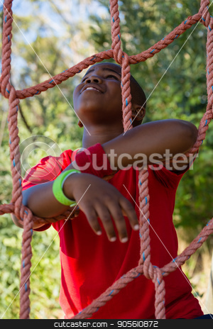 Happy boy leaning on net during obstacle course stock photo, Happy boy leaning on net during obstacle course in the boot camp by Wavebreak Media