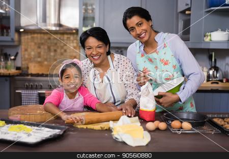 Smiling multi-generation family preparing food in kitchen stock photo, Portrait of smiling multi-generation family preparing food in kitchen at home by Wavebreak Media