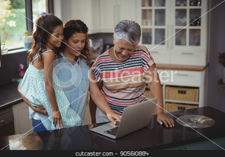 Happy family using laptop in kitchen stock photo, Happy family using laptop in kitchen at home by Wavebreak Media