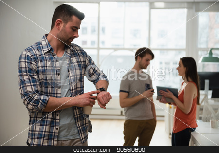 Female executive adjusting a smart watch while colleague discussing in background stock photo, Female executive adjusting a smart watch while colleague discussing in background at office by Wavebreak Media