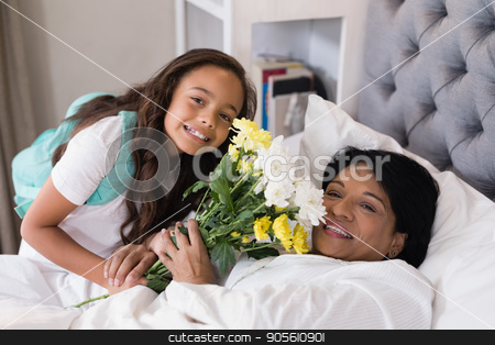 Portrait of smiling grandmother and granddaughter with flower bouquet on bed at home stock photo, High angle portrait of smiling grandmother and granddaughter with flower bouquet on bed at home by Wavebreak Media