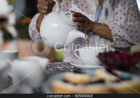Mid section of woman pouring tea in cup stock photo, Mid section of woman pouring tea in cup on table at home by Wavebreak Media
