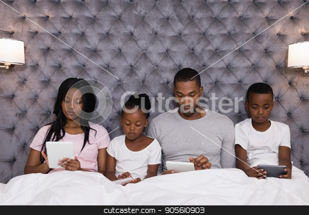Family using digital tablets while sitting together on bed stock photo, Family using digital tablets while sitting together on bed at home by Wavebreak Media