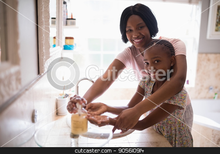 Smiling mother assisting daughter while washing hands in bathroom at home stock photo, Portrait of smiling mother assisting daughter while washing hands in bathroom at home by Wavebreak Media