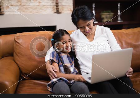 Smiling woman with granddaughter using laptop at home stock photo, Smiling woman with granddaughter using laptop while sitting on sofa at home by Wavebreak Media
